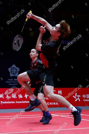 Soh Wooi Yik, Aaron Chia. Malaysia's Soh Wooi Yik, right, hits a return shot next to his teammate Aaron Chia during their men's doubles badminton match against Taiwan's Lu Ching Yao and Yang Po Han at the World Tour Finals in Guangzhou in south China's Guangdong province