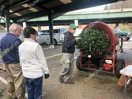 "Bob and Jane Atkins, left, of Madison, W.Va., watch Robert Cole of French Creek Farms place their Christmas tree into a wrapping machine before being loaded onto their vehicle at the Capitol Market in Charleston, W.Va. Bob Atkins said not only are Christmas tree prices higher this year, but ""there's not as many as usual, it seems to me"
