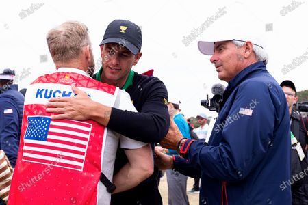 Adam Scott of Australia congratulates Matt Kuchar of team USA caddie and Fred Couples of team USA after the final round of The Presidents Cup