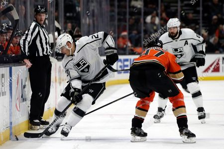 Los Angeles Kings right wing Dustin Brown (23) takes the puck across the blue line against Anaheim Ducks defenseman Hampus Lindholm (47) with defenseman Drew Doughty (8) watching during the first period of an NHL hockey game in Anaheim, Calif