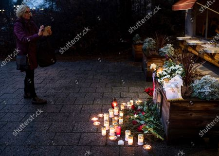 Stock Photo of A fan takes pictures at a makeshift memorial for Swedish pop singer and songwriter Marie Fredriksson outside Baggpipe Studios (formerly known as EMI) in Skarmabrink, southern Stockholm