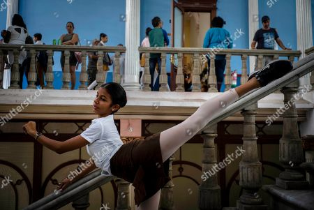 A ballet student poses for a friend to take photos, at the national ballet school in Havana, Cuba, . The Soviet-style system that recruits children into a system of increasingly selective state dance schools has produced hundreds of elite dancers including Lorna Feijoo, Rolando Sarabia, Taras Domitro, Anette Delgado and Carlos Acosta