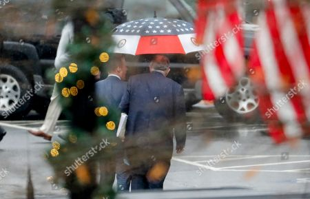 Rudy Giuliani, center, personal attorney for President Donald Trump, is seen leaving the West Wing of the White House in Washington