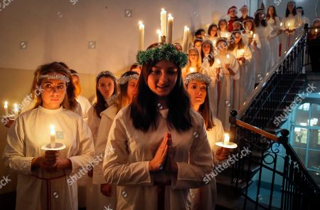 Young women walk with candles in procession to celebrate St. Lucia's Day in the Evangelical Lutheran Church of Saint Katarina in St.Petersburg, Russia, . The Church was built in the 19th century by and for Swedish expatriates in Saint Petersburg, and it is usually called the Swedish church. In Soviet era the Church used as a sport hall. St. Lucia is the patron saint of vision