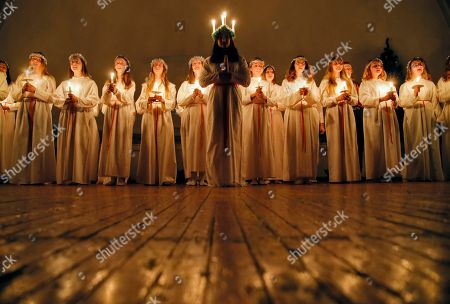 Young women sing carols as they hold candles to celebrate St. Lucia's Day in the Evangelical Lutheran Church of Saint Katarina in St.Petersburg, Russia, . The Church was built in the 19th century by and for Swedish expatriates in Saint Petersburg, and it is usually called the Swedish church. In Soviet era the Church used as a sport hall. St. Lucia is the patron saint of vision