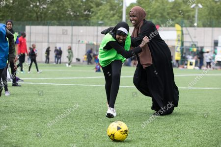 Stock Photo of A muslim woman dressed in an Islamic robe plays football with young school children aged 10-13 years old