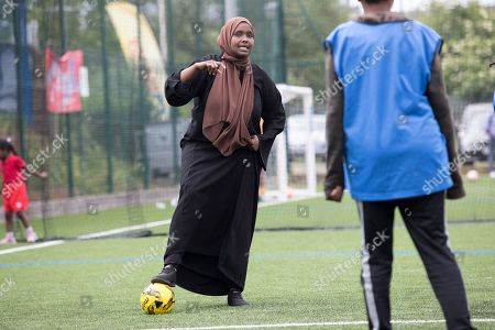 A muslim woman dressed in an Islamic robe plays football with young school children aged 10-13 years old