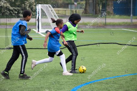 Girls of 9-12 years old at a football training session. Many are Muslim and wear headscarves