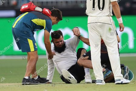 Umpire Aleem Dar is helped to his feet by medical staff after New Zealand's Mitchell Santner ran into him during play in their cricket test against Australia in Perth, Australia
