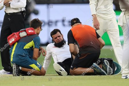 Umpire Aleem Dar is attended to by medical staff after New Zealand's Mitchell Santner ran into him during play in their cricket test against Australia in Perth, Australia
