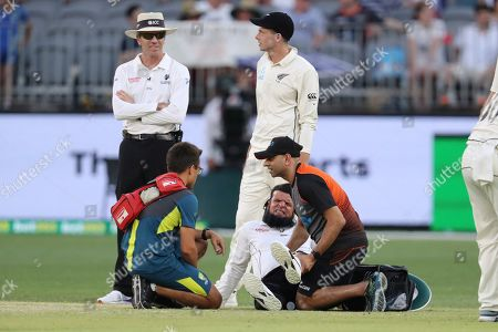Umpire Aleem Dar is helped to his feet by medical staff after New Zealand's Mitchell Santner (right, rear) ran into him during play in their cricket test against Australia in Perth, Australia