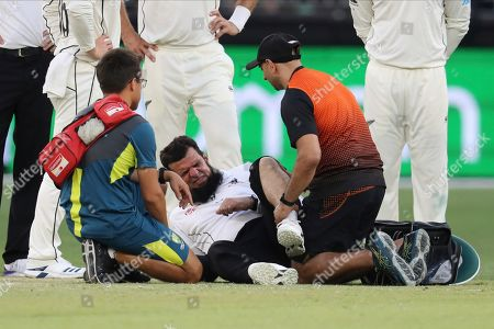 Umpire Aleem Dar is attended to by medical staff after New Zealand's Mitchell Santer ran into him during play in their cricket test against Australia in Perth, Australia