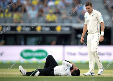 Cricket umpire Aleem Dar (L) reacts after colliding with New Zealand player Mitchell Satner as Tim Southee (R) looks on during day three of the first Test match between Australia and New Zealand at Optus Stadium in Perth, Australia, 14 December 2019.