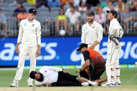Cricket umpire Aleem Dar (2-L) receives treatment to his knee after colliding with New Zealand player Mitchell Satner during day three of the first Test match between Australia and New Zealand at Optus Stadium in Perth, Australia, 14 December 2019.
