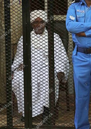 epa08070338 Sudan's ousted president Omar Hassan al-Bashir sits in the defendant's cage during his trial in Khartoum, Sudan, 14 December 2019. A Sudanese court in Khartoum on 14 December 2019 found former president al-Bashir guilty of money laundering and sentenced him to two years in rehabilitation facility. The verdict is the first in several cases against al-Bashir who was ousted in April 2019 after some 30 years in power.