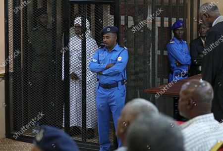 Stock Picture of epa08070338 Sudan's ousted president Omar Hassan al-Bashir sits in the defendant's cage during his trial in Khartoum, Sudan, 14 December 2019. A Sudanese court in Khartoum on 14 December 2019 found former president al-Bashir guilty of money laundering and sentenced him to two years in rehabilitation facility. The verdict is the first in several cases against al-Bashir who was ousted in April 2019 after some 30 years in power.
