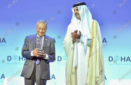 Emir of Qatar Sheikh Tamim bin Hamad al-Thani (R) awards Malaysian Prime Minister Mahathir Mohamad (L) during the opening session of the Doha Forum at Sheraton Grand Doha Resort & Convention Hotel in Doha, Qatar, 14 December 2019. The Doha Forum, a global platform for dialogue gathering world leader and policy makers among others to build innovative and action driven networks, runs on 14 and 15 December.