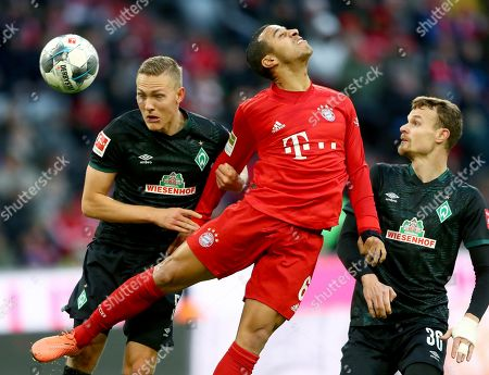 Bremen's Ludwig Augustinsson, left, and Bayern's Thiago, center, challenge for the ball during the German Bundesliga soccer match between FC Bayern Munich and SV Werder Bremen in Munich, Germany