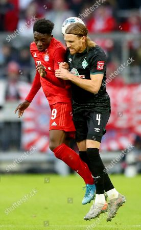 Bayern's Alphonso Davies, left, and Bremen's Michael Lang, right, challenge for the ball during the German Bundesliga soccer match between FC Bayern Munich and SV Werder Bremen in Munich, Germany