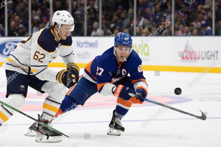 Buffalo Sabres defenseman Brandon Montour (62) and New York Islanders left wing Anders Lee (27) chase a loose puck in the third period of an NHL hockey game, in Uniondale, N.Y. The Islanders won 3-2 in overtime