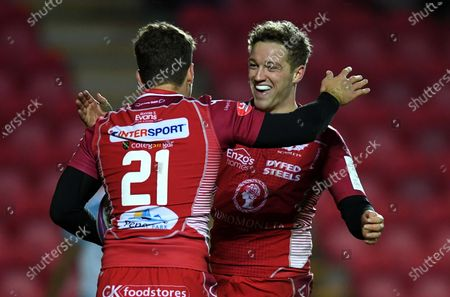 Kieran Hardy (21) of Scarlets celebrates his try with Angus O'Brien.