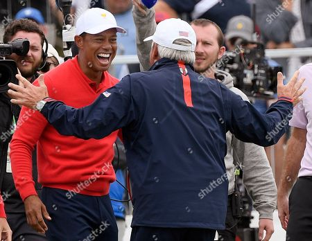 U.S. team player and captain Tiger Woods, left, celebrates with vice captain Fred Couples after Woods won his singles match during the President's Cup golf tournament at Royal Melbourne Golf Club in Melbourne