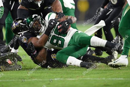 Baltimore Ravens defensive back Anthony Levine (41) tackles New York Jets running back Ty Montgomery (88) during an NFL football game, in Baltimore