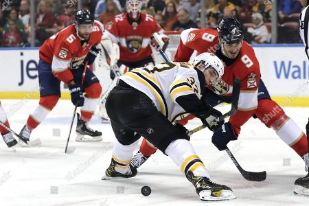 Boston Bruins defenseman Zdeno Chara (33) and Florida Panthers center Brian Boyle (9) go for the puck during the first period of an NHL hockey game, in Sunrise, Fla