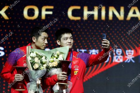 Xu Xin (L) and Fan Zhendong (R) of China take a selfie as they celebrate at the award ceremony after they defeated Liao Cheng-Ting and Lin Yun-Ju of Chinese Taipei during their Men's doubles finals match of the ITTF World Tour Grand Finals Table Tennis tournament in Zhengzhou, China, 15 December 2019.
