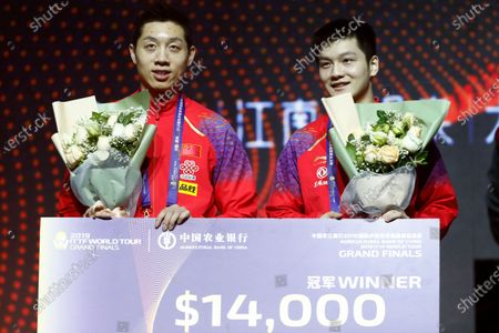 Xu Xin (L) and Fan Zhendong (R) of China celebrate at the award ceremony after they defeated Liao Cheng-Ting and Lin Yun-Ju of Chinese Taipei during their Men's doubles finals match of the ITTF World Tour Grand Finals Table Tennis tournament in Zhengzhou, China, 15 December 2019.