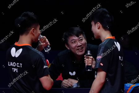 Stock Picture of A coach talks to Liao Cheng-Ting (L) and Lin Yun-Ju (R) of Chinese Taipei during a break in action against Xu Xin and Fan Zhendong of China during the Men's doubles finals match of the ITTF World Tour Grand Finals Table Tennis tournament in Zhengzhou, China, 15 December 2019.