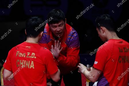 Stock Photo of The Coach talks to Xu Xin (R) and Fan Zhendong (L) of China during a break in action against Liao Cheng-Ting and Lin Yun-Ju of Chinese Taipei during the Men's doubles finals match of the ITTF World Tour Grand Finals Table Tennis tournament in Zhengzhou, China, 15 December 2019.