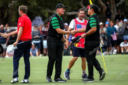 Ernie Els of South Africa and the International team shakes hands with Byeong Hun An of Korea and the International team