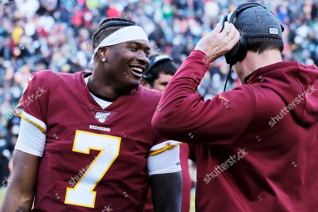 Washington Redskins quarterback Dwayne Haskins (left) talks with offensive coordinator kevin O'Connell during an NFL football game against the Philadelphia Eagles, in Landover, Md
