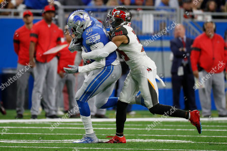 Detroit Lions running back Wes Hills is tackled by Tampa Bay Buccaneers strong safety Andrew Adams during the second half of an NFL football game, in Detroit