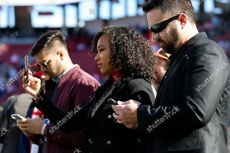 Reporter MJ Acosta, center, watches as players warm up before an NFL football game between the San Francisco 49ers and the Atlanta Falcons in Santa Clara, Calif