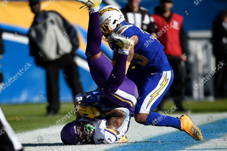 Minnesota Vikings wide receiver Bisi Johnson holds on to the pass for a touchdown as Los Angeles Chargers free safety Derwin James defends during the first half of an NFL football game, in Carson, Calif