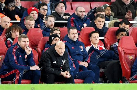 Stock Image of Arsenal's interim manager Freddie Ljungberg (2-L) sits on the bench next to assistant manager Per Mertesacker (L) and Mesut Oezil (2-R) during the English Premier League soccer match between Arsenal FC and Manchester City in London, Britain, 15 December 2019.