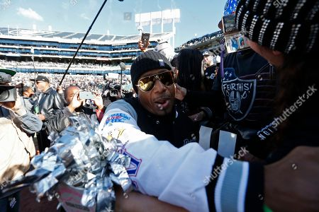 MC Hammer greets fans before the start of an NFL football game between the Oakland Raiders and the Jacksonville Jaguars in Oakland, Calif