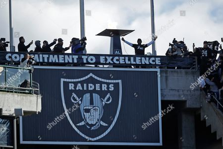 Stock Picture of Charles Woodson raises his arms after lighting a flame before the start of an NFL football game between the Oakland Raiders and the Jacksonville Jaguars in Oakland, Calif