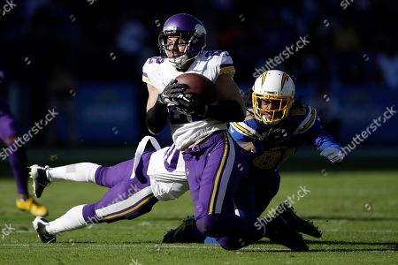 Minnesota Vikings free safety Harrison Smith, front,intercepts a pass intended for Los Angeles Chargers wide receiver Mike Williams, right, during the first half of an NFL football game, in Carson, Calif