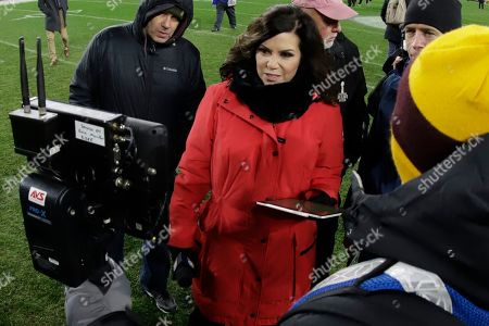 Stock Photo of NBC Sports Reporter Michele Tafoya, center, works on the field following an NFL football game between the Pittsburgh Steelers and the Buffalo Bills in Pittsburgh