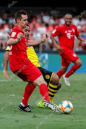 Borussia Dortmund's former player Patrick Owomoyela (R) in action against Bayern Munich's Miroslav Klose (L) during a game of the Cup Legends at the Morumbi Stadium in Sao Paulo, Brazil, 15 December 2019.