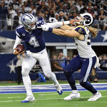 Dallas Cowboys quarterback DAK PRESCOTT #4 gives a stiff arm to Los Angeles Rams outside linebacker CLAY MATTHEWS #52 in the first quarter for a first down during NFL action at AT&T Stadium
