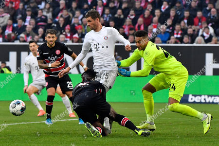 In this photo Bayern's Thomas Mueller, center, Duesseldorf's goalkeeper Zack Steffen, right, Duesseldorf's Kasim Nuhu, bottom, and Duesseldorf's Matthias Zimmermann background, challenge for the ball during the German Bundesliga soccer match between Fortuna Duesseldorf and FC Bayern Munich in Duesseldorf, Germany