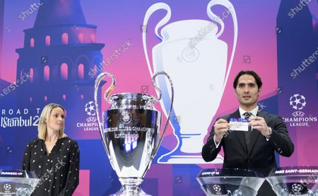 Stock Photo of Turkish soccer player Hamit Altintop (R) shows the lot of France's soccer club Paris Saint-Germain during the UEFA Champions League 2019/20 round of 16 draw ceremony at the UEFA Headquarters in Nyon, Switzerland, 16 December 2019.