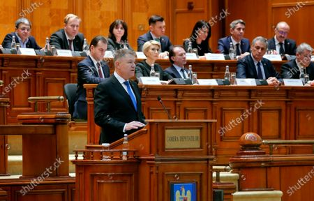Stock Picture of Romanian President Klaus Iohannis (front, on podium), backed by government members, delivers a speech in front of lawmakers to commemorate the victims of the 1989 anti-Communist revolution, in the Romanian Parliament in Bucharest, Romania, 16 December 2019. During December 1989, the anti-Communist revolution generated in the western city of Timisoara with dozens of people killed in the streets while shouting 'Down Ceausescu!' and 'Freedom!'. Romanians pay their respect to the activists, who in 1989 took to the streets in the civil unrest that toppled Eastern Europe's most repressive communist regime. More than 1,100 people were killed across Romania during clashes between demonstrators and forces loyal to then dictator Nicolae Ceausescu.