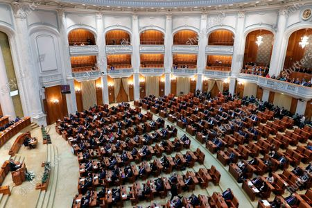 Stock Image of Romanian President Klaus Iohannis (L, on podium) delivers a speech in front of lawmakers to commemorate the victims of the 1989 anti-Communist revolution, in the Romanian Parliament in Bucharest, Romania, 16 December 2019. During December 1989, the anti-Communist revolution generated in the western city of Timisoara with dozens of people killed in the streets while shouting 'Down Ceausescu!' and 'Freedom!'. Romanians pay their respect to the activists, who in 1989 took to the streets in the civil unrest that toppled Eastern Europe's most repressive communist regime. More than 1,100 people were killed across Romania during clashes between demonstrators and forces loyal to then dictator Nicolae Ceausescu.