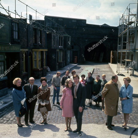 Cast members on the exterior Coronation Street set. Front row: Doris Speed (as Annie Walker), Arthur Leslie (as Jack Walker), Eileen Derbyshire (as Emily Nugent), Anne Reid (as Valerie Barlow), William Roache (as Ken Barlow), John Sharp (as Les Clegg) and Irene Sutcliffe (as Maggie Clegg) Back row: Graham Haberfield (as Jerry Booth), Peter Adamson (as Len Fairclough), Pat Phoenix (as Elsie Tanner), Jennifer Moss (as Lucille Hewitt), Violet Carson (as Ena Sharples), Margot Bryant (as Minnie Caldwell) and Mitzi Rogers (as Jenny Sutton)