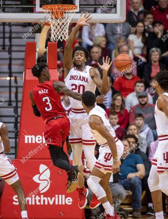 Cam Mack, De'Ron Davis. Nebraska guard Cam Mack (3) passes the ball off to a teammate as his route to the basket is blocked by Indiana forward De'Ron Davis (20) during the first half of an NCAA college basketball game, in Bloomington, Ind